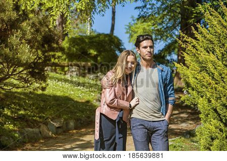 Boyfriend and girlfriend standing in countryside in green luscious field, strolling and cuddling, showing romantic love