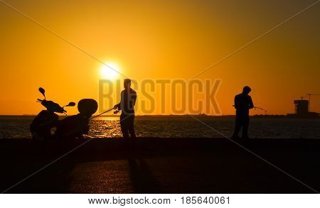 Men silhouette with fishing rod at sunset. There is a motorcycle silhouette near the man.