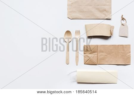 food delivery service workdesk with paper bags and flatware on restourant gray table background top view mockup