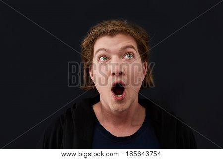 Close up of straight face of surprised and shocked caucasian man. Happy face on dark background.