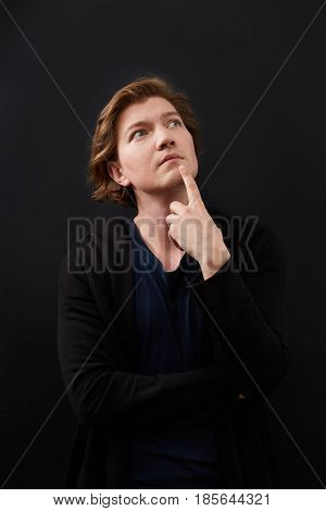 Portrait of young, pensive man looks up in casuals isolated on black background.
