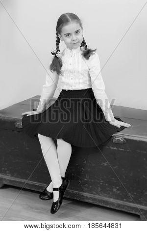 A beautiful little schoolgirl girl in a white blouse and black long skirt, with neatly braided pigtails on her head.She sits on an old trunk. Interior of the fifties of the last century.Black-and-white photo. Retro style.