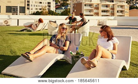 Two beautiful woman laughing and smiling at each other while laying on sunbeds on an urban rooftop with some alcoholic beverages in an ice bucket between them.
