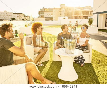 Attractive group of people socialising in an urban envronment on a green lawn on a warm summer afternoon, enjoying the sun on their skin during sunset.