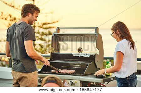 Handsome guy smiling while flirting with an attractive woman, while he turns the meat on the grid with her by his side helping him get the food cooked and making conversation.