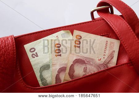 Thai baht notes in a red leather bag.