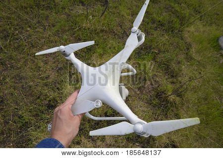 Russia Poltavskaya village - May 9 2017: The crashed drone. Dirty and in the juice of the grass is a quadrocopter. DJI Phantom 4