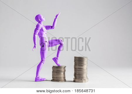 Empowered Women Stepping Up The Income Ladder Concept. Purple Female Figurine Clilmbing Up On Piles