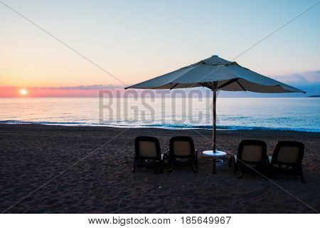 Sunshade umbrella on sea beach. Tranquil view of the Mediterranean sea. Amazing pink sunrise with clear sky. Location place: Turkey, Kemer.