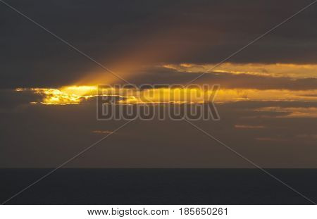 A bright golden heavenly shaft of light breaks through an opening in the clouds over a dark sea around sunset