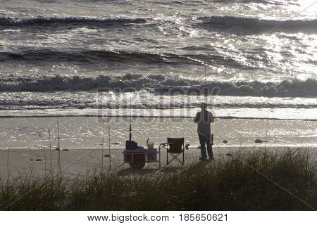 The silhouette of a man fishing in a silvered sea with fishing poles chair cooler and other equipment nearby