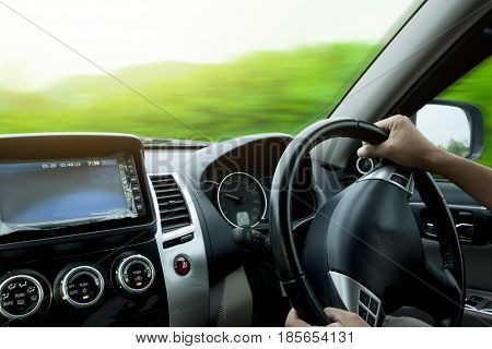 Hands on steering wheel of a car driving on an asphalt blurred road beside have green tree.