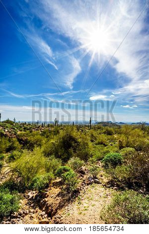 Bright Sun Rays in blue sky over the Valley of the Sun in Arizona with the city of Phoenix in the distant background