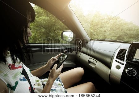 Asia Women use mobile phone in the car for lost help or support.