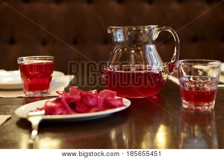 Red juice in jar and glasses on table