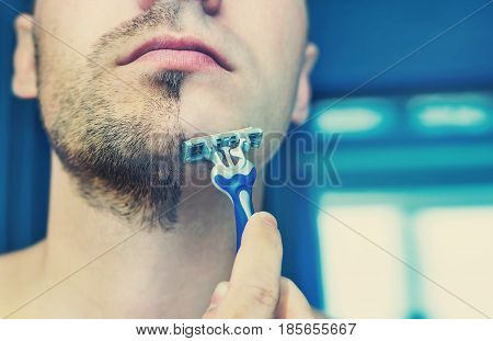 Young man shaves his short beard shaving machine tool. Half face with a beard half shaved.