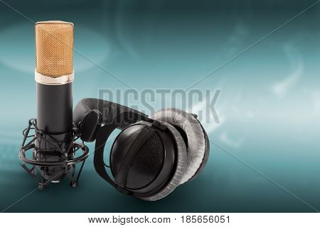 Headphones and condenser microphone on the green background.