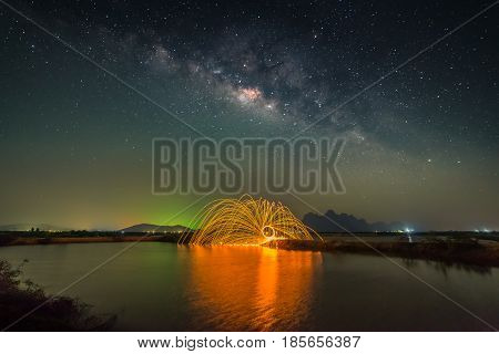 Milky way with fireworks over swamp in rural of Thailand