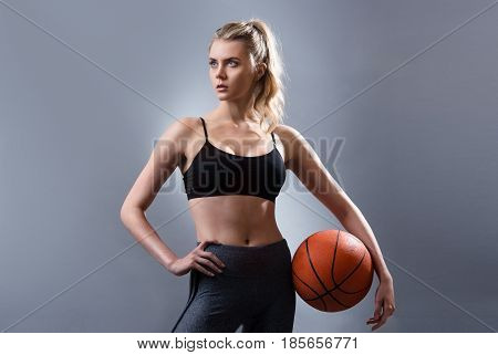 Beautiful woman basketball player standing and holding basketball ball