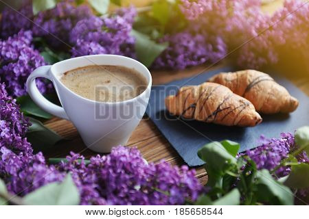 Spring cet and fresh breakfast on a wooden table. Lilac croissants and a cappuccino cup are on the table. A bouquet of lilac on a wooden table.