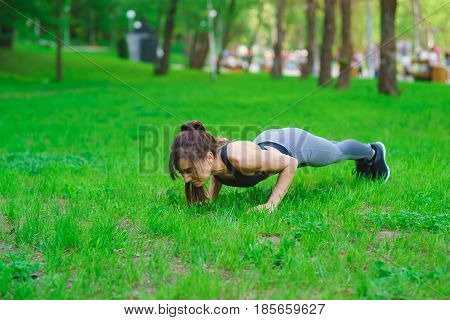 Sports girl brunette wringing out in the park on the grass