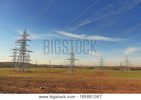 Power lines on the field in early spring. Transmission of electricity through power lines. Blue sky and white clouds, field, forest.