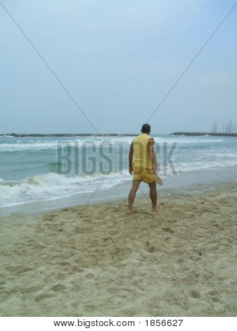 Man On The Beach Carrying Bat For Playing Tennis