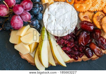 Cheese Plate Grape Salted Craker Cookies Dry Dates Cranberry, Fig, Pear Pretzels On A Wooden Board O