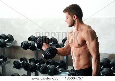 Shot of a shirtless sportive doing exercises with dumbbells at the gym working out shoeing off his sexy muscular strong body fitness sports masculinity athleticism athlete concept.