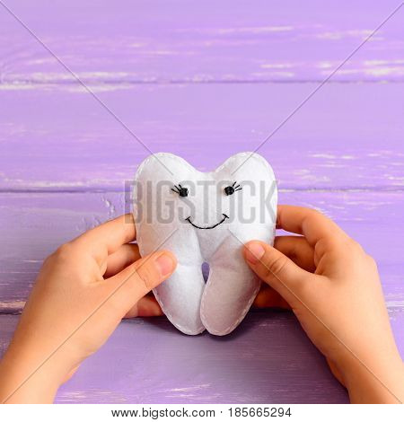 Little child made a felt tooth fairy toy. Child holds a felt tooth fairy toy in his hands. Purple wooden background. Easy and funny kids crafts. Closeup
