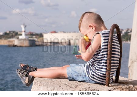 Beautiful little boy in sailor stripes vest siting on a breakwater on the background of the sea lighthouse and old fort and looking down on his hand through binoculars smiling
