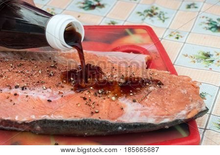 Fillet of raw red fish sprinkled with spices and poured with soy sauce