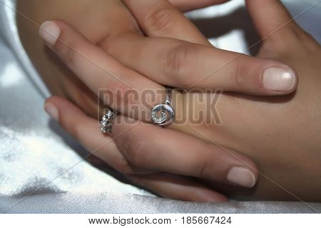 female hands with rings made of white gold with diamonds
