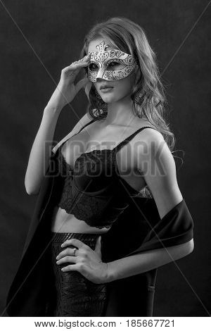 beautiful woman in mask undressing on black background, monochrome