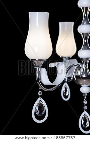 Silver metallic candelabra close-up with candles isolated on black background.