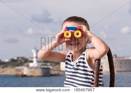 smiling little boy in a sailor vest looking into the distance through binoculars sitting against the background of the ocean and shore with lighthouse
