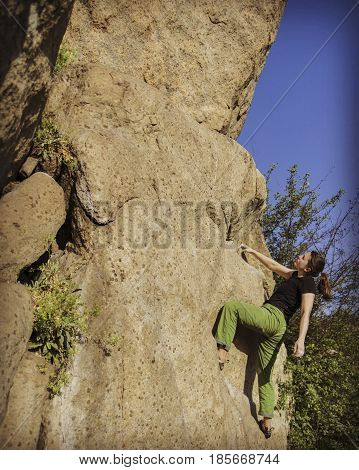 Rock climber reaching for his next hand hold Joshua Tree National Park.