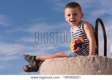 adorable small boy in vest and sandals with binoculars sitting on breakwater on the blue sky background
