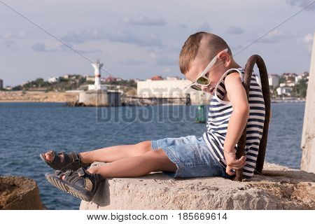 funny little boy in sunglasses and a sailor stripes vest sitting on concrete breakwater with sea and shore with lighthouse background