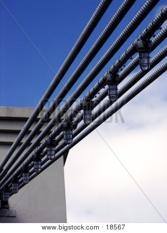 lights hang in line along the cables of the suspension foot bridge in waco, texas. poster