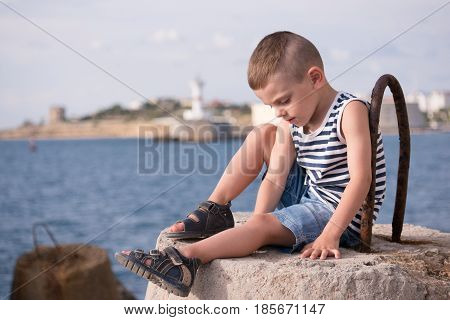 beautiful little boy in vest and shorts sitting on breakwater against the sea and shore in summer