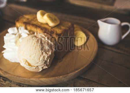 Honey toast whit ice cream on wood dish. Vintage color tone.