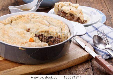 Homemade meat pie from puff pastry with beef and vegetables on wooden table