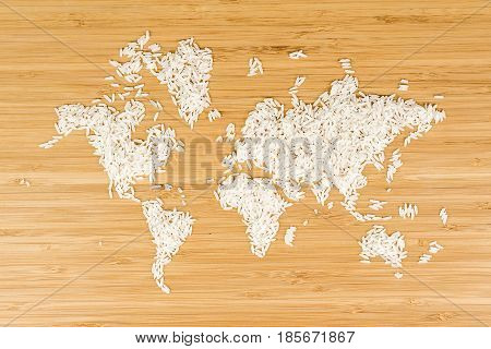 map of the world made of white rice on bamboo wood background