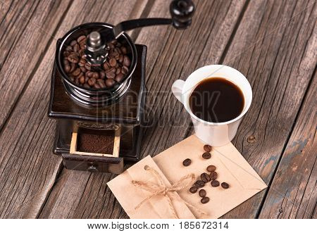 Vintage coffee grinder with a cup of espresso over old wooden background