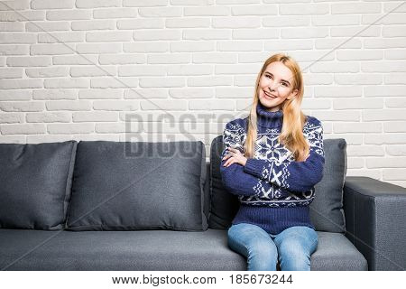 Smiling Woman Relaxing On The Sofa At Home While Looking At Camera And Smiling.