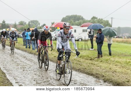 Ennevelin France - July 092014: Group of cyclists riding on a cobblestone road during the stage 5 of Le Tour de France 2014.