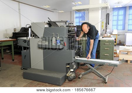 People Working At An Offset Printing Machine
