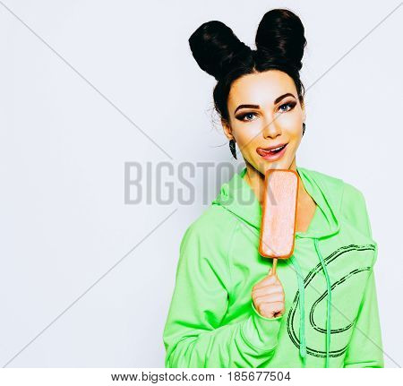 Eskimo. Young beautiful girl in a bright outfit gets pleasure from ice cream. Frozen dessert. Indoor. White background.