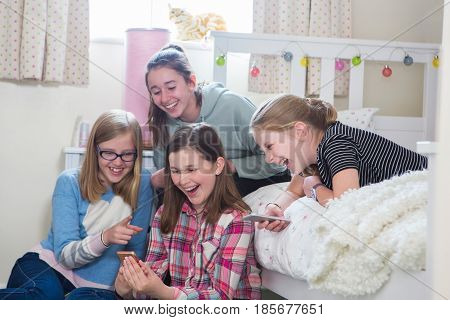 Group Of Young Girls With Mobile Phones In Bedroom